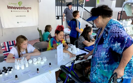 Camp Innoventure students pitch their handmade products to a potential customer at the Las Cruces Farmers and Crafts Market in July 2019. The students created business and marketing plans, along with their inventory of products, during the weeklong entrepreneurship camp offered by Arrowhead Center at New Mexico State University.