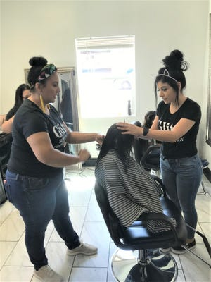 Glitz School of Cosmetology students in Las Cruces give a child a free haircut Wednesday, Aug. 7. The cosmetology school completed 381 free haircuts for school aged children in the community.