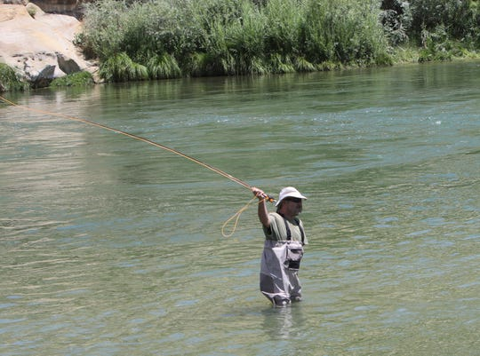An angler prepares to heave his line into the water of the Texas Hole, Thursday, Aug. 8, 2019, on the San Juan River.