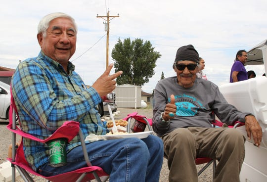Upper Fruitland residents Aaron King, left, and Mel Begaye enjoy lunch at the Doo'Alk'aii Community Field Day on Aug. 9 at the Walter Collins Center in Upper Fruitland.