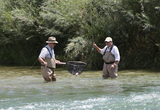 Two anglers work together to net a trout, Thursday, Aug. 8, 2019, at the Texas Hole on the San Juan River.