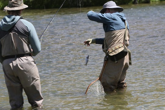 Dallas resident Phillip Glass reaches to unhook a small trout caught by Layton Glasson on Aug. 8 near the Texas Hole on the San Juan River.