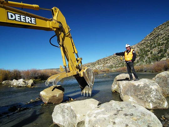 A New Mexico Department of Game and Fish biologist directs a heavy equipment operator on the placement of large boulders to improve trout habitat in the San Juan River.