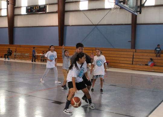 Children play basketball as part of the Doo'Alk'aii Community Field Day on Aug. 9 at the Walter Collins Center in Upper Fruitland.