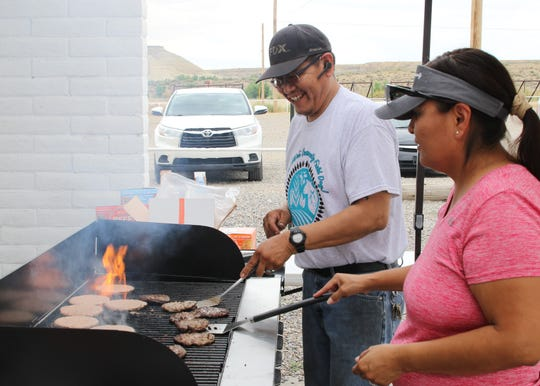From left, Silas Bedah and Chrissy Ford help cook lunch for participants at the Doo'Alk'aii Community Field Day on Aug. 9 at the Walter Collins Center in Upper Fruitland.