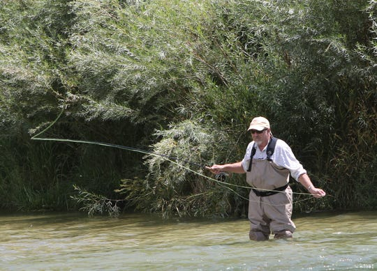 An angler casts his line while fishing the Texas Hole, Thursday, Aug. 8, 2019, on the San Juan River.