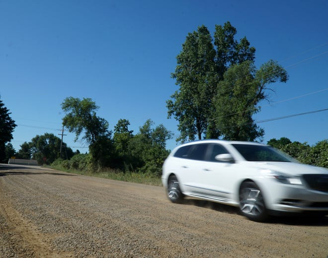 A car zips along Currie Road north of Eight Mile Road. Some residents along Currie Road would like a stricter speed enforcement as some drivers exceed speed limits on the gravel road that twists and turns.