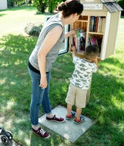 Some neighbors of Nicole Mehelich visit the Little Free Library outside her Livonia home.