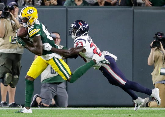 Green Bay Packers' J'Mon Moore catches a pass for a touchdown over Houston Texans' Johnson Bademosi during the second half of their preseason football game Thursday, August 8, 2019, at Lambeau Field in Green Bay, Wis.