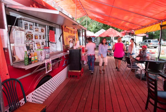 Diners gather at the Tacos El Amigo food truck on Tippin Avenue for a taste of authentic Mexican food on Friday. El Amigo is one of two food trucks regularly stationed at the location. The other is Pupusas Ely, which features Salvadoran cuisine.
