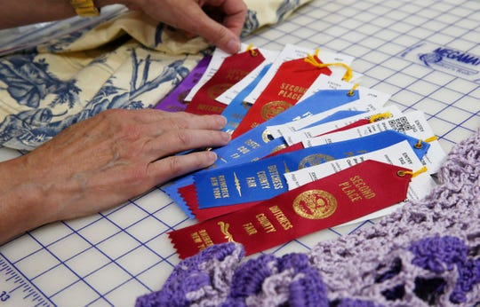 Peggy Norton sorts through her award ribbons from the Dutchess County Fair at her home in Staatsburg on August 7, 2019.