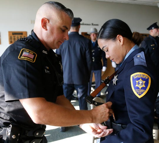 Dutchess County Sheriffs deputy Paul Reinheim assists deputy recruit Danesha Miller with her equipment belt prior to the Dutchess County Law Enforcement Academy graduation ceremony on August 9, 2019.
