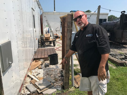 Larry Parsons, owner of Woody's Beach BBQ, points at the location where a restroom used to sit behind his business.