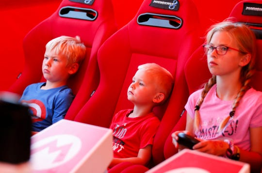 Siblings Finn (left), 6, Tucker (center), 4, and Raegan Vannoy, 11, play Mario Kart 8 Deluxe against each other in the Nintendo Switch Road Trip tour tent at the Iowa State Fair on Friday, Aug. 9, 2019.