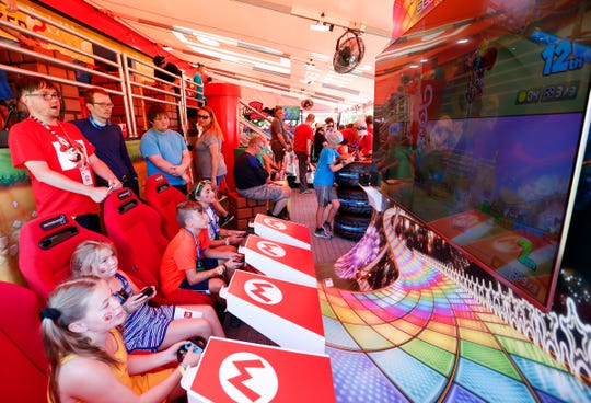 From the left, Emeline Myers, 11, Laurel Myers, 9, Jett Jansen, 12,Jovi Jansen, 10, play Mario Kart 8 Deluxe against each other in the Nintendo Switch Road Trip tour tent at the Iowa State Fair on Friday, Aug. 9, 2019.