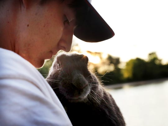 Caleb Smith, 15, with one of the rabbits at a marina where the organization keeps its houseboat, used to house rabbits transiting to and from Peace Bunny Island and where Smith and fellow rabbit enthusiasts sometimes spend the night and seen Monday, July 29, 2019, near Newport, MN. (David Joles/Star Tribune)
