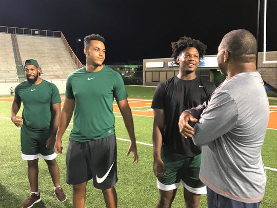 FAMU tight ends Kieran Goodrich (center) and Kamari Young talk with position coach James Spady. Marquan Cromartie observes the action in the background.
