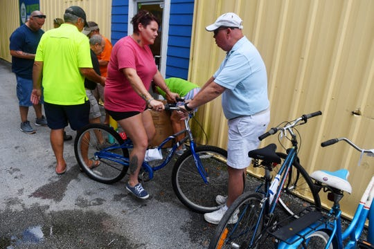Trisha Damron talks with Dave Hunter as she is fitted with a refurbished bicycle on Wednesday, Aug. 7, 2019, after completing an hour-long safety class at United Against Poverty in Vero Beach. Each participant is given a bike, helmet, lock and lights after competing the course operated by Bike Walk Indian River County in conjunction with United Against Poverty. Unless a new storage facility can be found to house the 200 bikes currently in inventory, the 8-year-old program could come to an end.