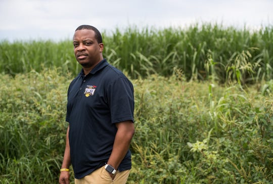Belle Glade native Pastor Steve Messam says the smoke from burning sugar cane fields, like the one pictured behind him near Glades Central Community High School on July 25, 2019, affects his family's health, including 5-year-old son Noah.