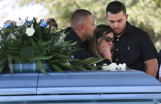 Juan de Dios Velásquez's son, Alvaro Mena, left, and grandson, Maximo Rosa, comfort daughter Linda Duarte as they say goodbye after he was killed outside Walmart during the mass shooting that killed 22 and wounded 25. Velásquez was the first person shot in the attack. He was buried at Mount Carmel Cemetery in East El Paso, Texas, on Friday, Aug. 9, 2019.