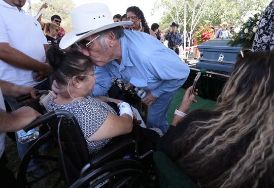 Nicolasa Velásquez is comforted during the funeral for her husband, Juan de Dios Velasquez, on Friday, Aug. 9, 2019, at Mount Carmel Cemetery in east El Paso, Texas. She was transported to the cemetery in an ambulance after she was shot along with her husband on Aug. 3, 2019, outside the Walmart near Cielo Vista Mall.
