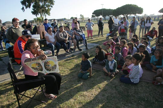 "Carolina Gallardo-Magaña, chairwoman of the Southwinds Neighborhood Council, reads ""The Bossy Gallito"" by Lucía Gonzalez during a storytime Thursday at Southwinds Park in Oxnard."