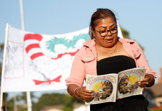 "Carolina Gallardo-Magaña, chairwoman of the Southwinds Neighborhood Council in Oxnard, reads ""The Bossy Gallito"" by Lucía Gonzalez on Thursday during a storytime at Southwinds Park. The event was organized by Lucy Cartagena, director of the nonprofit Family First. Stories were read by Oxnard neighborhood residents."