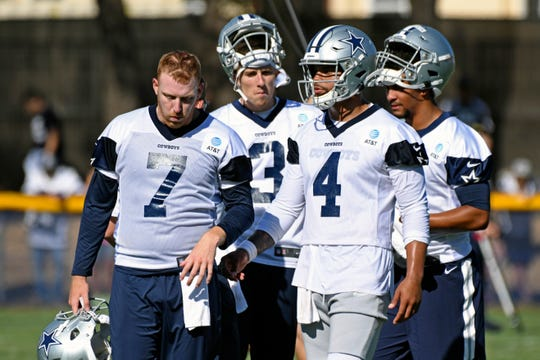 Dallas Cowboys quarterbacks Cooper Rush (7), Mike White (3), Dak Prescott (4) and Taryn Christion, right, gather at the NFL football team's training camp in Oxnard, Calif., Saturday, July 27, 2019. (AP Photo/Michael Owen Baker)