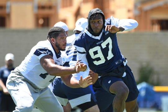 Dallas Cowboys defensive end Taco Charlton (97) rushes against offensive tackle La'el Collins at the NFL football team's training camp in Oxnard, Calif., Saturday, July 27, 2019. (AP Photo/Michael Owen Baker)