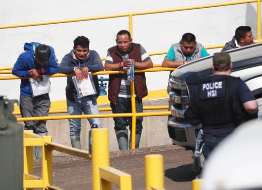 Handcuffed workers await transportation to a processing center following a raid by U.S. immigration officials at Koch Foods Inc., plant in Morton, Miss.