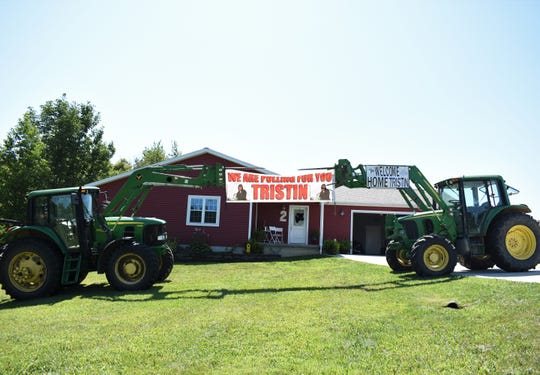 A crowd of family and friends clad in blue Pulling for Tristin T-shirts greeted Tristin Boring outside his house when he arrived home just before noon on Friday. Two tractors were alsoin the yard andheld banners welcoming Tristin home.