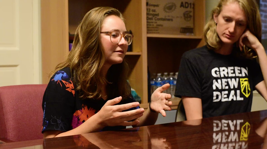 Lauren Maunus(right) and Revelle Mast(left) speak in their office space at Sunrise Movement, a youth-led movement advocating political action on climate change, in Washington, D.C.