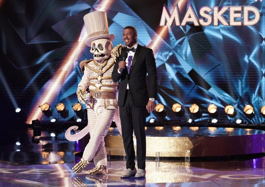 Skeleton, left, leans on host Nick Cannon during an episode of Fox's 'The Masked Singer.'