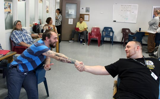 In this Aug. 5, 2019 photo, Israel Rivera, left, and Michael Manning greet each other during a group counseling session at the Hampden County Sheriff's Department's minimum security, residential treatment facility in Springfield, Mass.