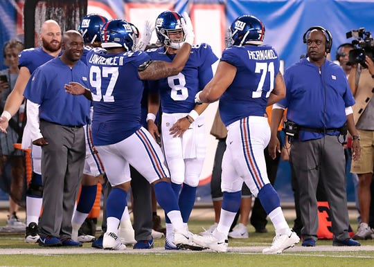 New York Giants quarterback Daniel Jones (8) celebrates after throwing a touchdowns pass with defensive tackle Dexter Lawrence (97) and offensive guard Will Hernandez (71) during the first half against the New York Jets at MetLife Stadium.