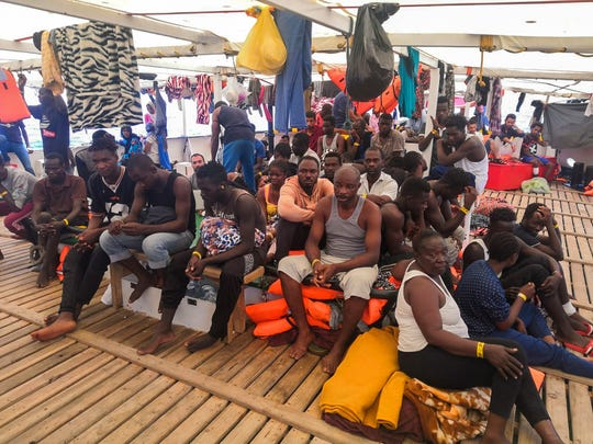 Migrants are seen aboard the Open Arms Spanish humanitarian boat as it cruises in the Mediterranean Sea, Friday, Aug. 9, 2019. Open Arms has been carrying 121 migrants for a week in the central Mediterranean awaiting a safe port to dock, after it was denied entry by Italy and Malta. (AP Photo/Valerio Nicolosi)