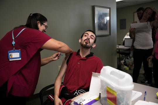 Summit County Public Health nurse Rachel Flossie gives a hepatitis A vaccination to Robert Wolf, 24, during a South Street Ministries program in Akron, Ohio, on July 23, 2019.