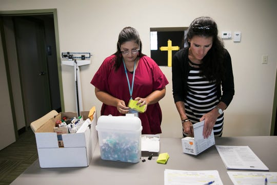 Summit County Public Health nurse Rachel Flossie, left, and communicable disease supervisor Tracy Rodriguez prepare to give vaccinations to clients during a South Street Ministries program in Akron, Ohio, on July 23, 2019.