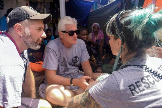 Actor Richard Gere, center, talks with staff members of the Open Arms Spanish humanitarian boat as it cruises in the Mediterranean Sea, Friday, Aug. 9, 2019.