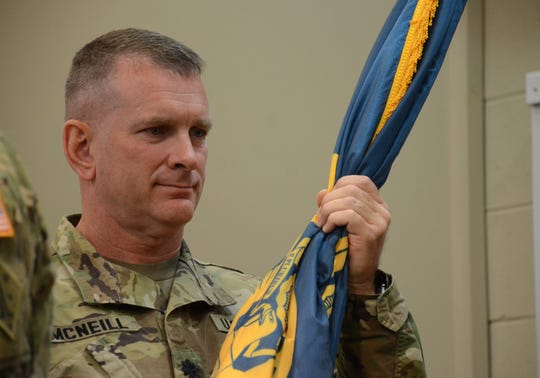 Lt. Col. Mark McNeill accepts the Fort Custer flag during a change of command ceremony Saturday.