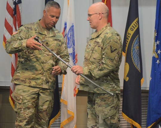 Lt. Col. Steve Wilson, left, accepts a  ceremonial sword from Col. Ed Hallenbeck, presented from personnel of Fort Custer Training Center, which Wilson commanded for almost four years.