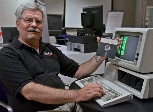 David Bradley, an original member of the IBM PC team and the inventor of the control-alt-delete function, sits in front of one of the original PC computers and holds up a copy of the DOS software it used Friday, July 27, 2001, at the IBM office in Durham, N.C.