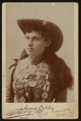 A collectible card of Annie Oakley shows  her shooting medals. The marksman's story is equal parts fact and myth