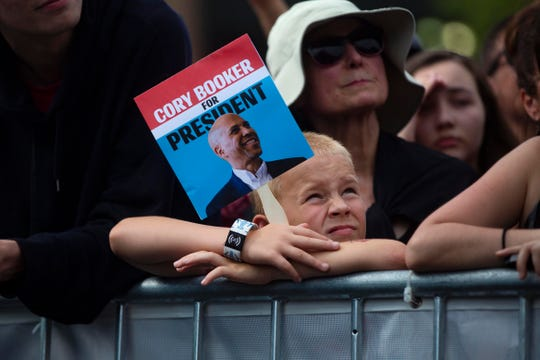 A young supporter listens as 2020 candidate Cory Booker speaks at the Des Moines Register Political Soapbox on August 10, 2019.
