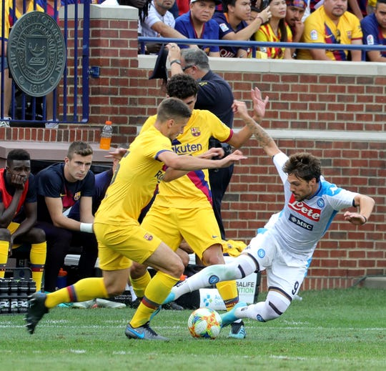 Napoli #9 Simone Verdi falls while going against the Barcelona defense during second half game action between FC Barcelona and Napoli at Michigan Stadium in Ann Arbor, Michigan on Saturday, August, 10, 2019.  Barcelona won the game 4-0.