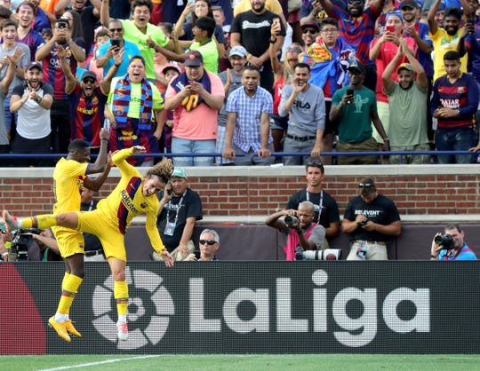 As fans watch and cheer, (L to R) Barcelona #11 Ousmane Dembele and teammate Antonie Griezmann celebrate Dembele's goal during second half game action between FC Barcelona and Napoli at Michigan Stadium in Ann Arbor, Michigan on Saturday, August, 10, 2019.  Barcelona won the game 4-0.