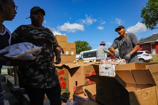 Demetrius Knuckles, 46, of Roseville sorts food donated by Gleaners Community Food Bank of Southeastern Michigan to hand out at Community First Tax Service in Inkster on Saturday, Aug. 10, 2019. After being released from prison in 2018, Knuckles has rededicated his life to building up the community by volunteering.