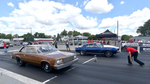 Two classic muscle cars drag race against each other.