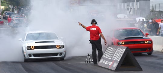 Two Dodge Hellcat Demons drag race against each other.