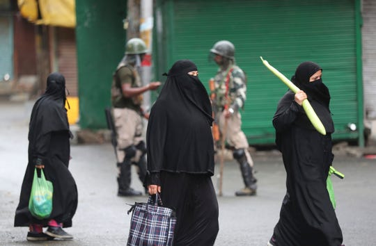 Kashmiri women holds bags filled with essentials and walk past Indian paramilitary soldiers closing off a street in Srinagar, Indian controlled Kashmir, Saturday, Aug. 10, 2019.